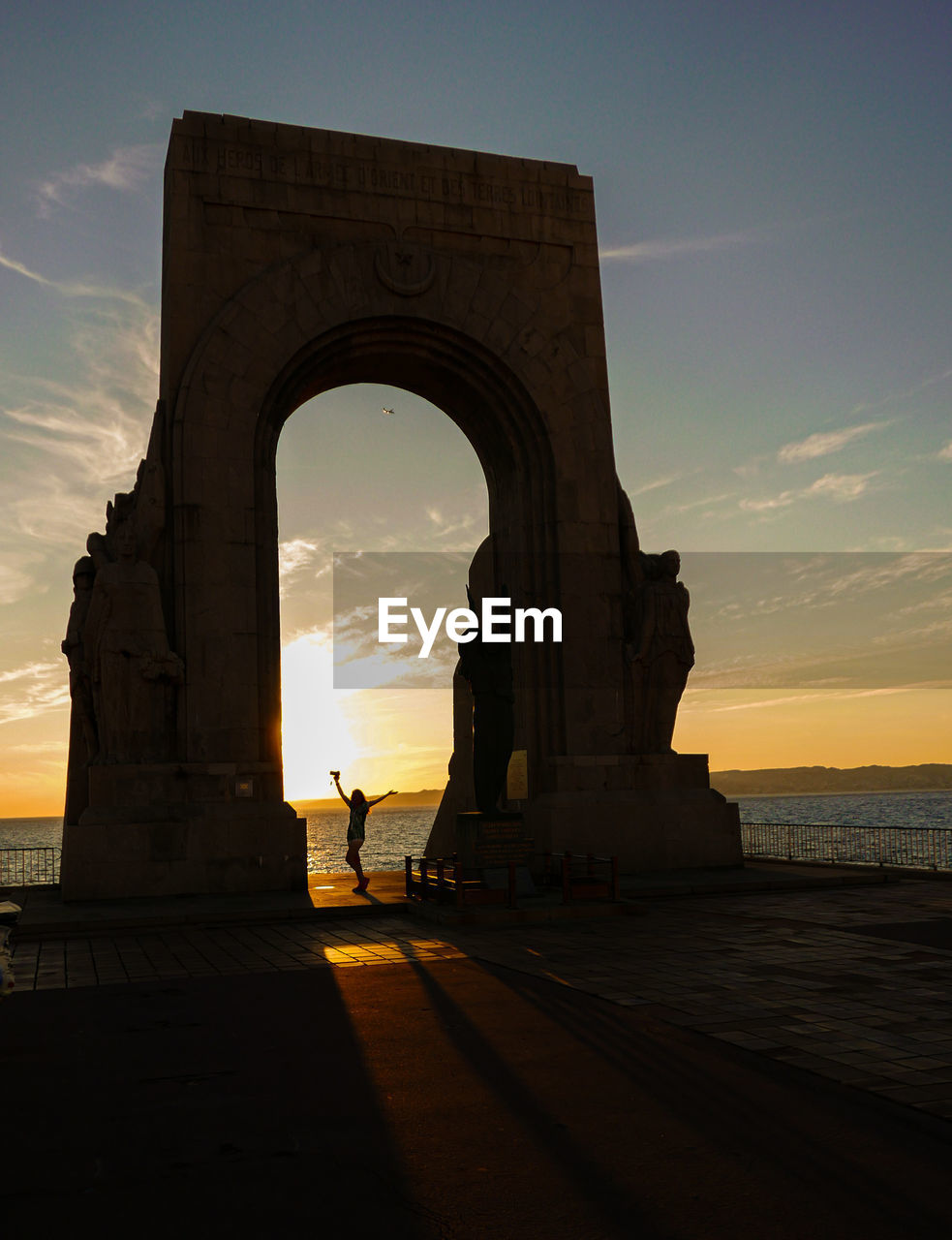 sky, sunset, architecture, sea, water, arch, built structure, silhouette, nature, real people, incidental people, cloud - sky, history, the past, travel destinations, orange color, sunlight, travel, tourism, outdoors