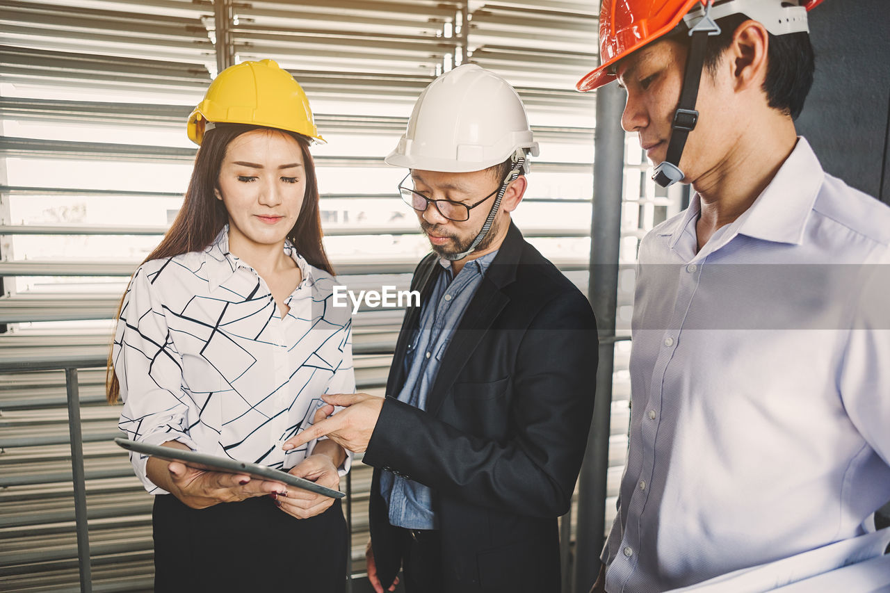 helmet, headwear, hardhat, occupation, hat, business, males, group of people, standing, cooperation, indoors, waist up, adult, young adult, men, teamwork, women, business person, communication, coworker, design professional, blueprint, mature adult, architect, mature men