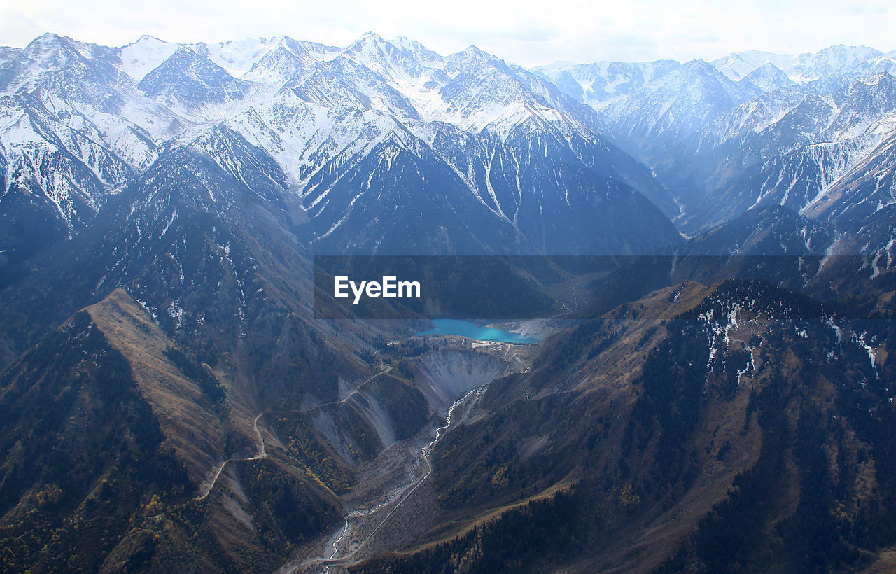 Top view of an alpine lake in a mountain gorge with peaks in the snow