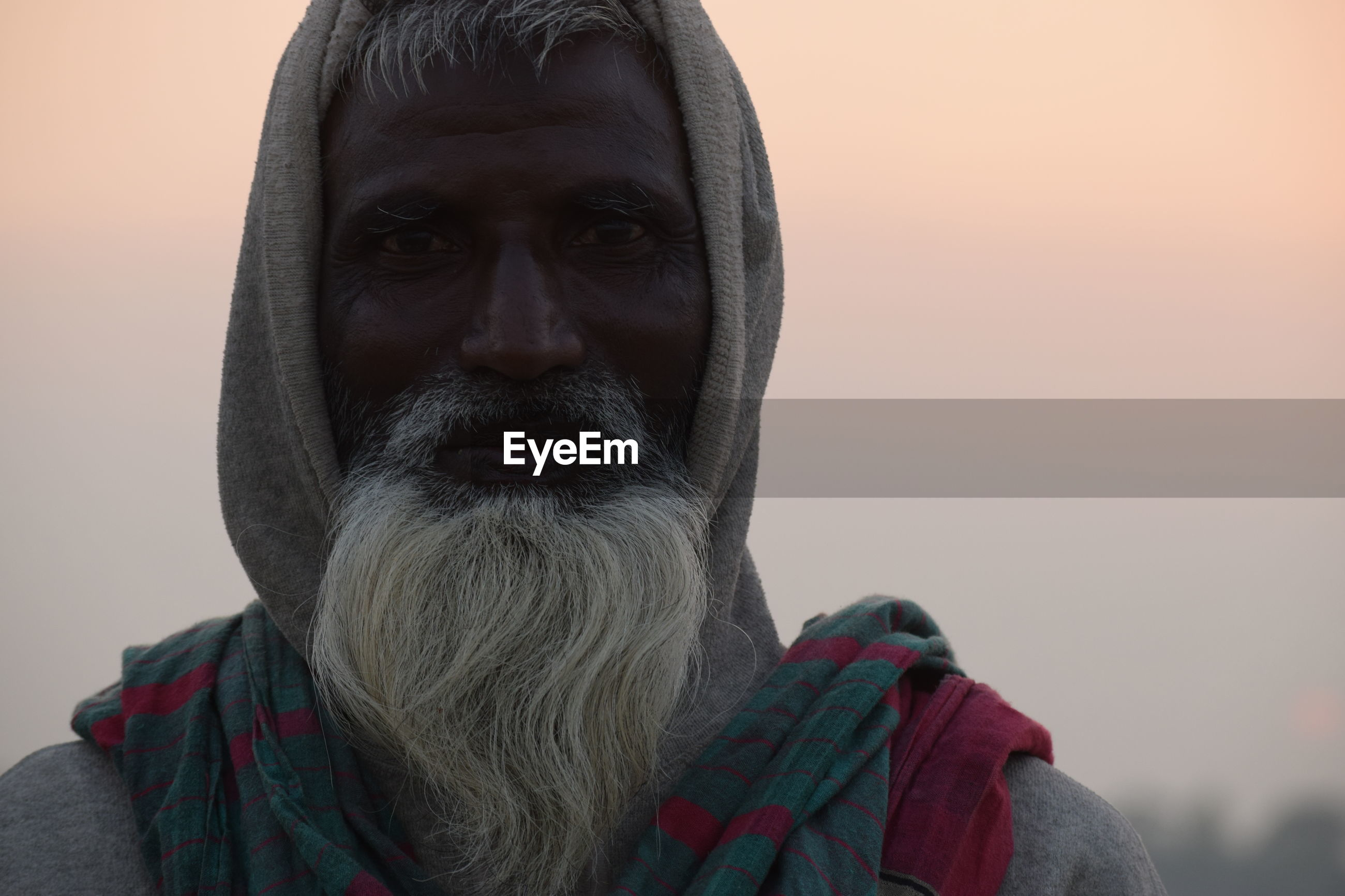 Close-up of portrait of bearded man against clear sky during sunset