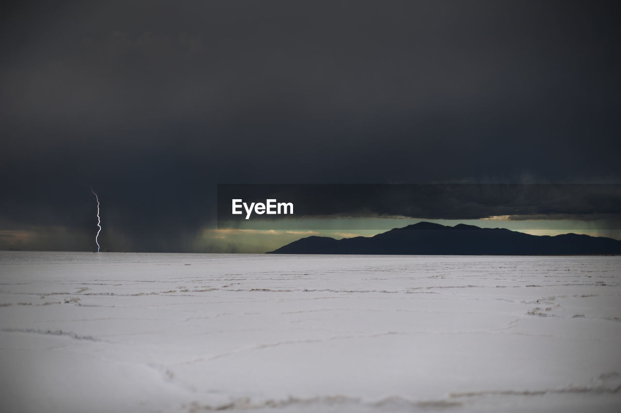 Idyllic Shot Of Lightning On Salt Flat Against Cloudy Sky