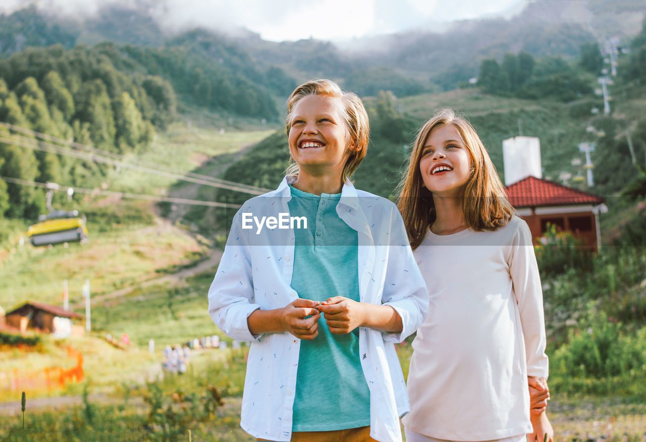 Portrait of smiling sibling standing against mountain