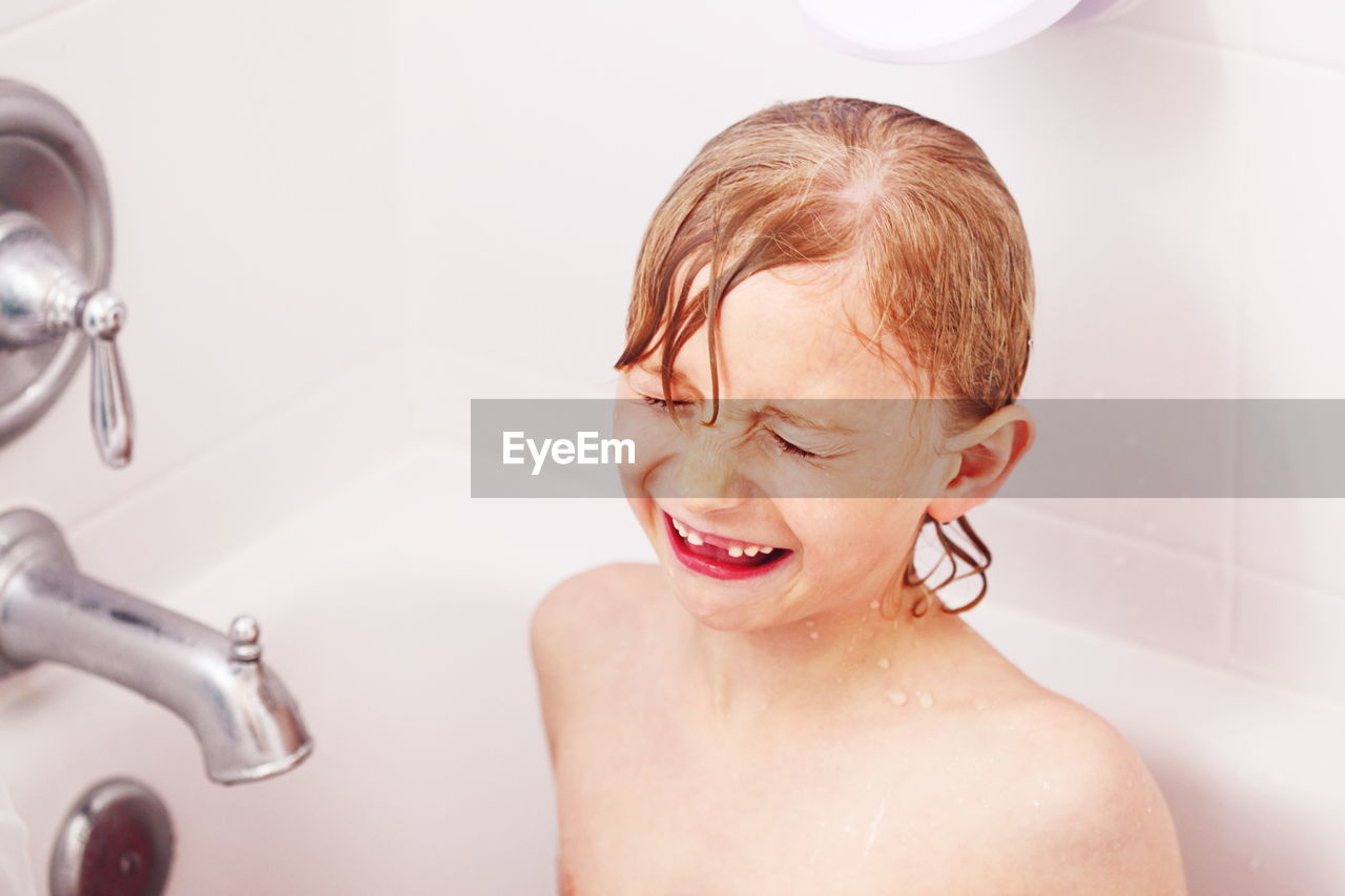 High Angle View Of Boy Making Face While Bathing In Tub