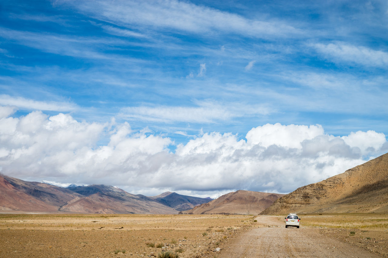 Car On Dirt Road Against Sky At Ladakh