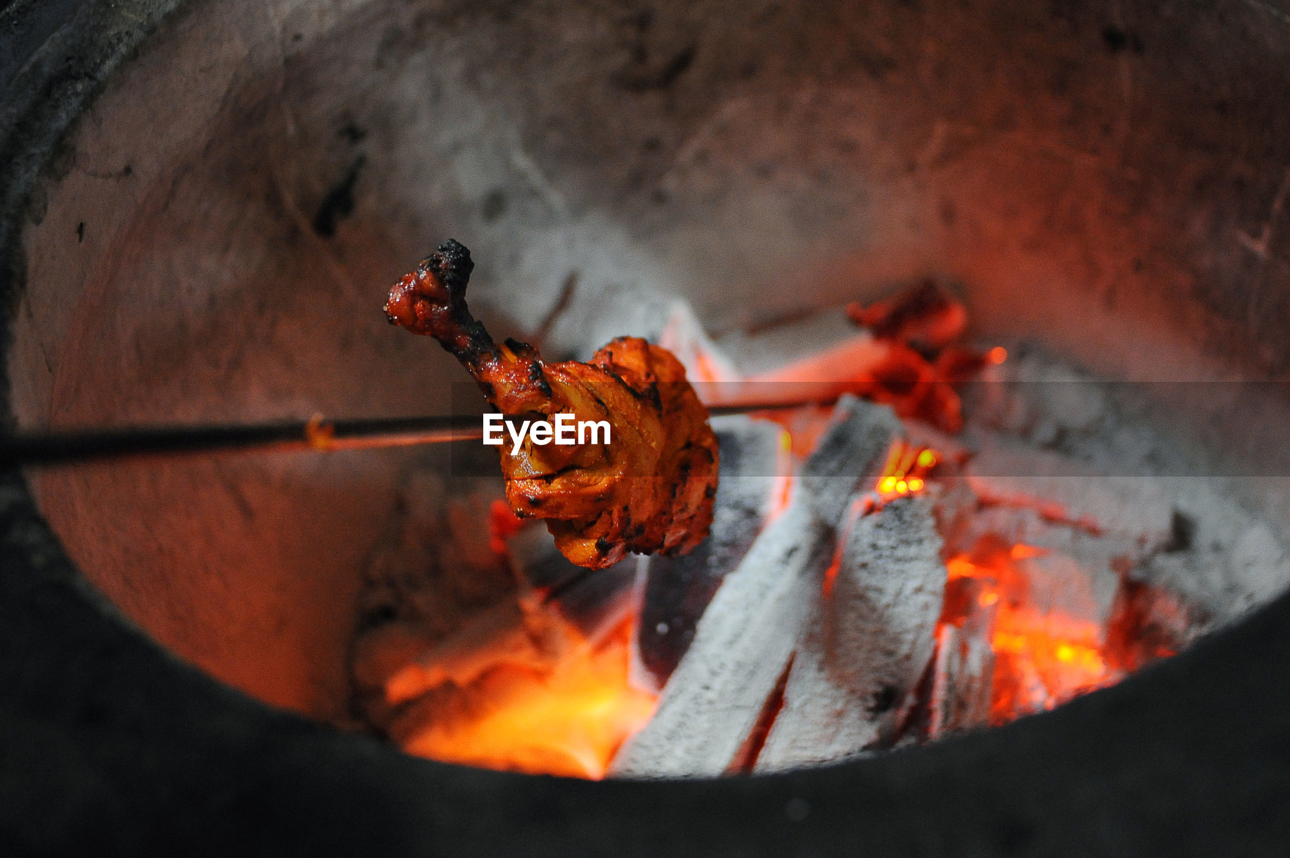 Close-up of chicken cooking in tandoor