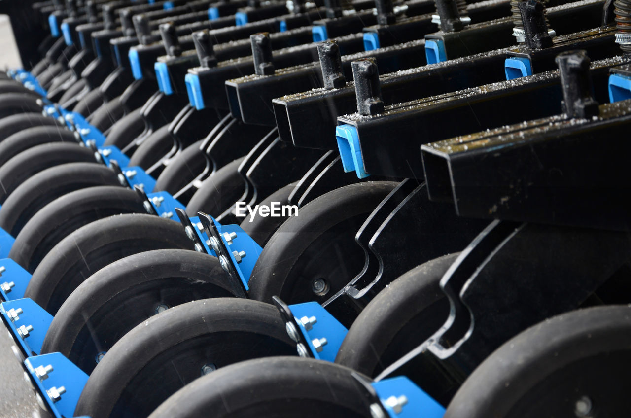 no people, full frame, repetition, in a row, blue, backgrounds, abundance, seat, large group of objects, indoors, empty, chair, sport, arrangement, selective focus, side by side, order, absence, stadium, close-up, wheel, tire