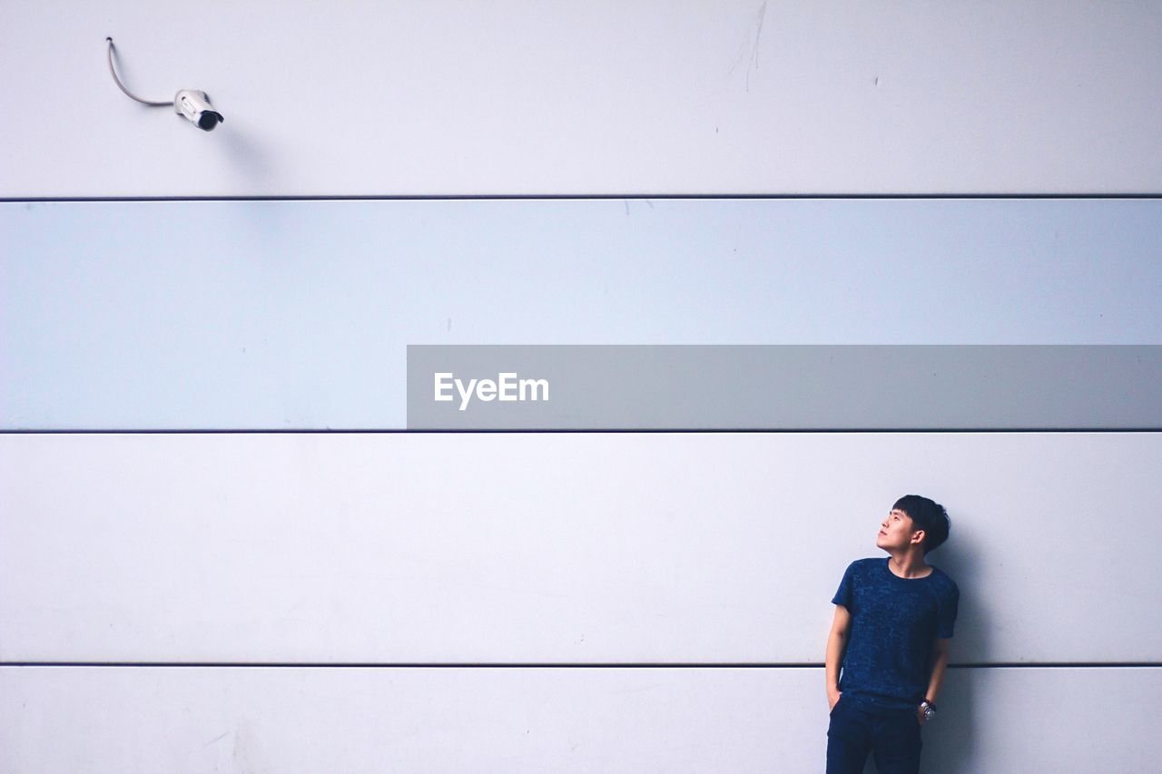 Young asian man standing against wall looking at surveillance camera