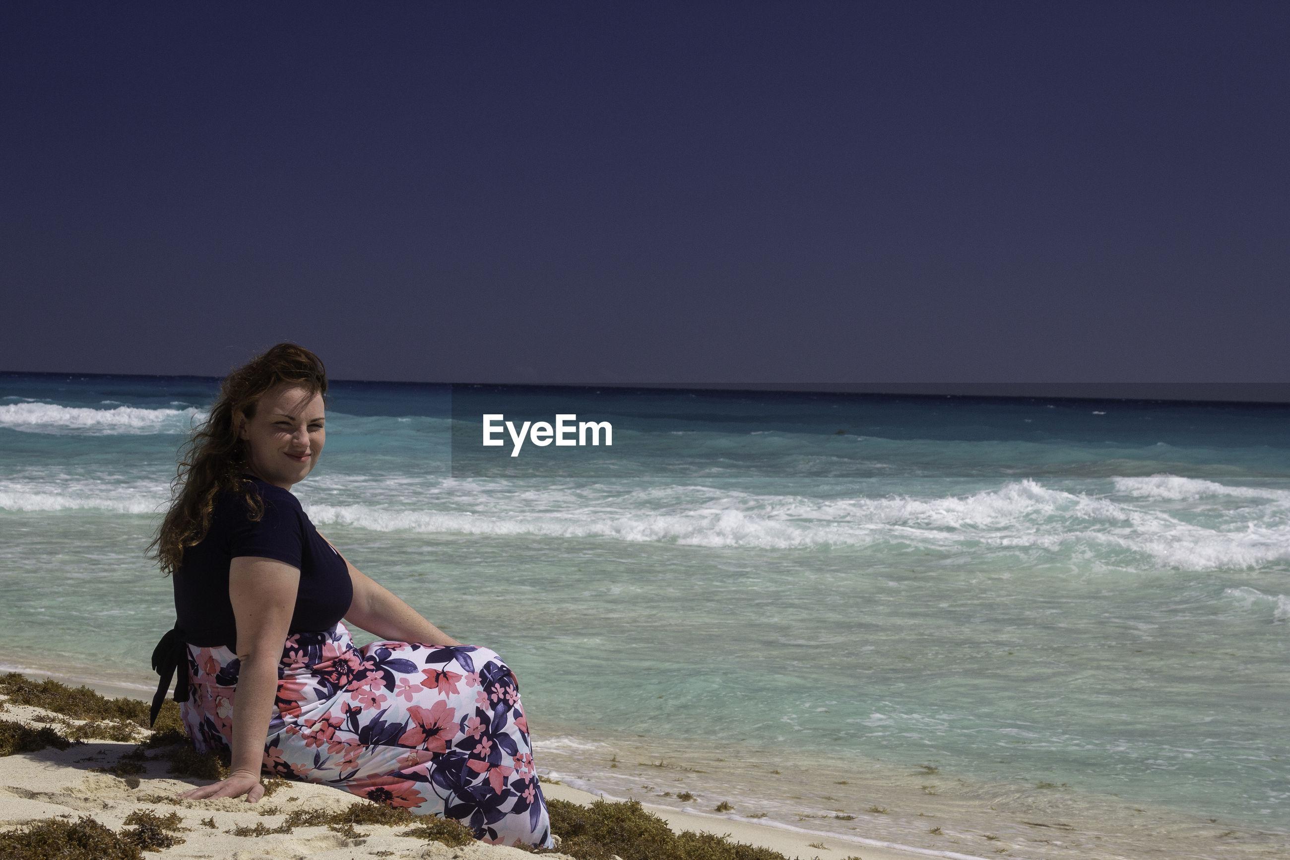 Portrait of woman sitting on beach against sky