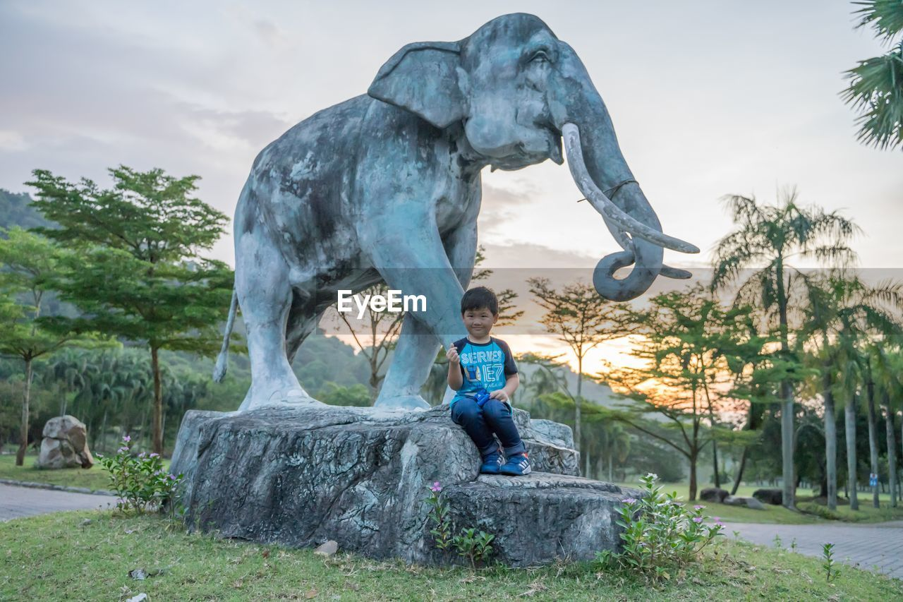 Portrait of boy sitting against statue during sunset