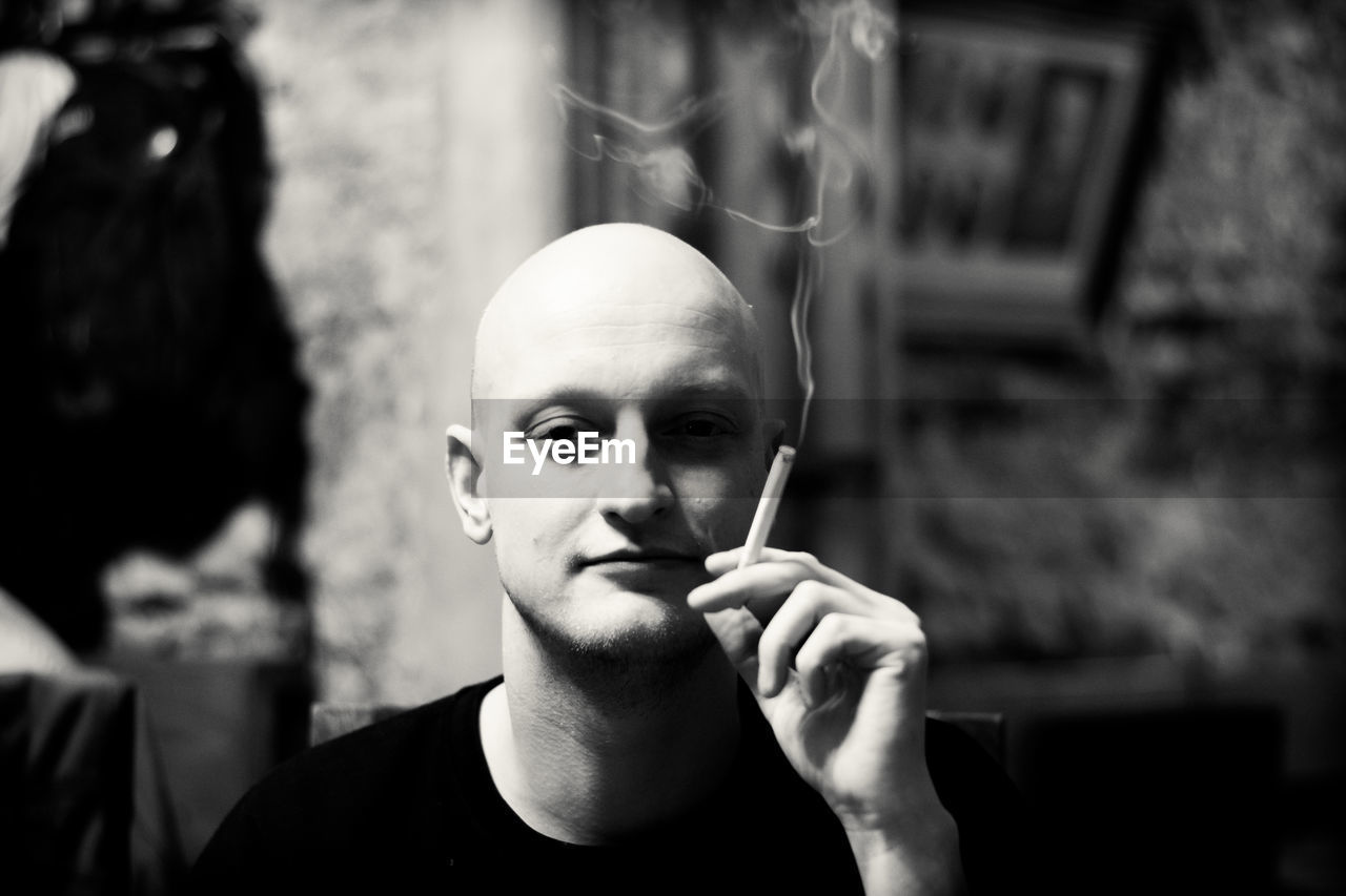 portrait, headshot, focus on foreground, one person, real people, lifestyles, holding, front view, smoking issues, young adult, communication, looking at camera, cigarette, smoking - activity, bad habit, smoke - physical structure, men, leisure activity, human face