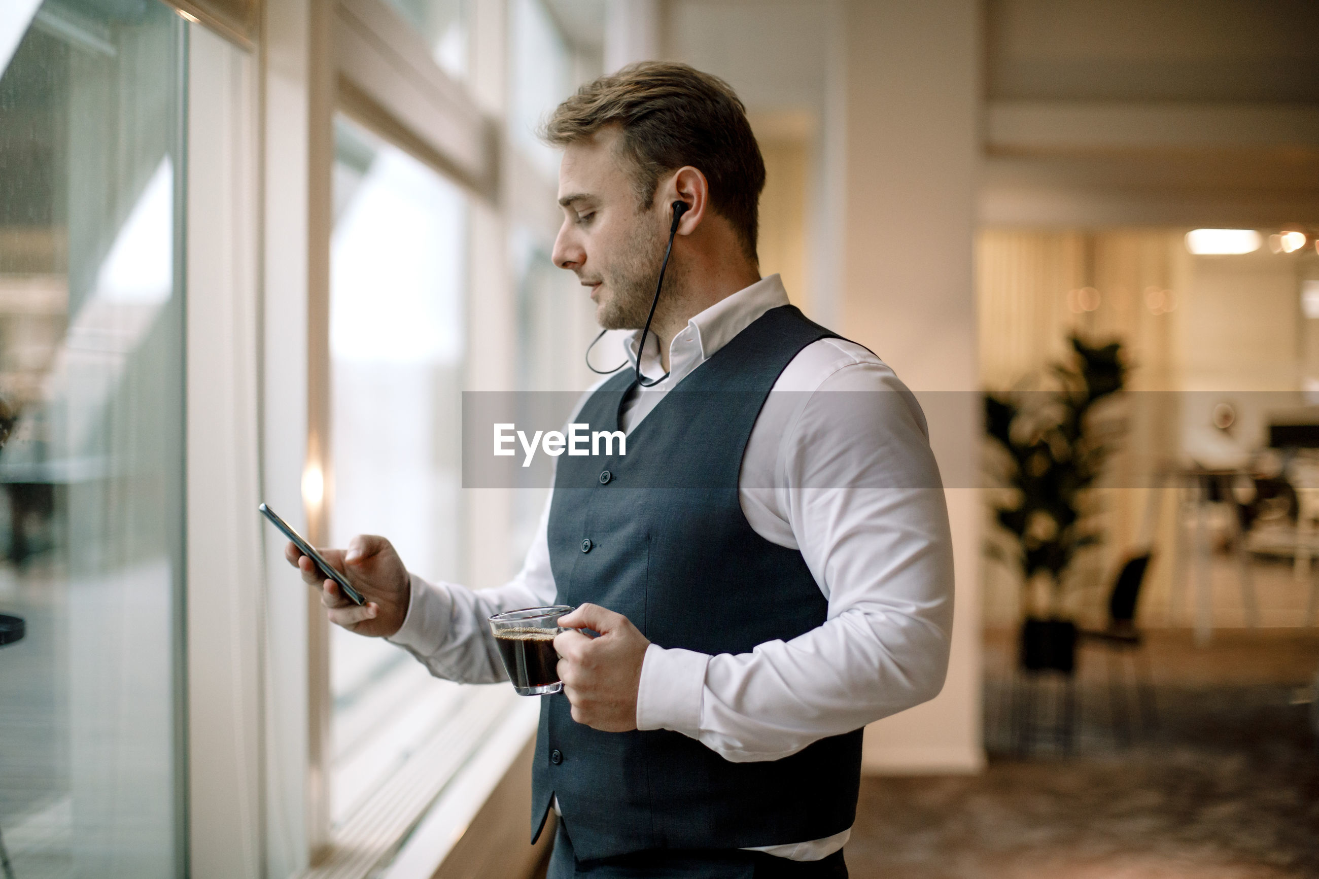 SIDE VIEW OF A YOUNG MAN USING PHONE