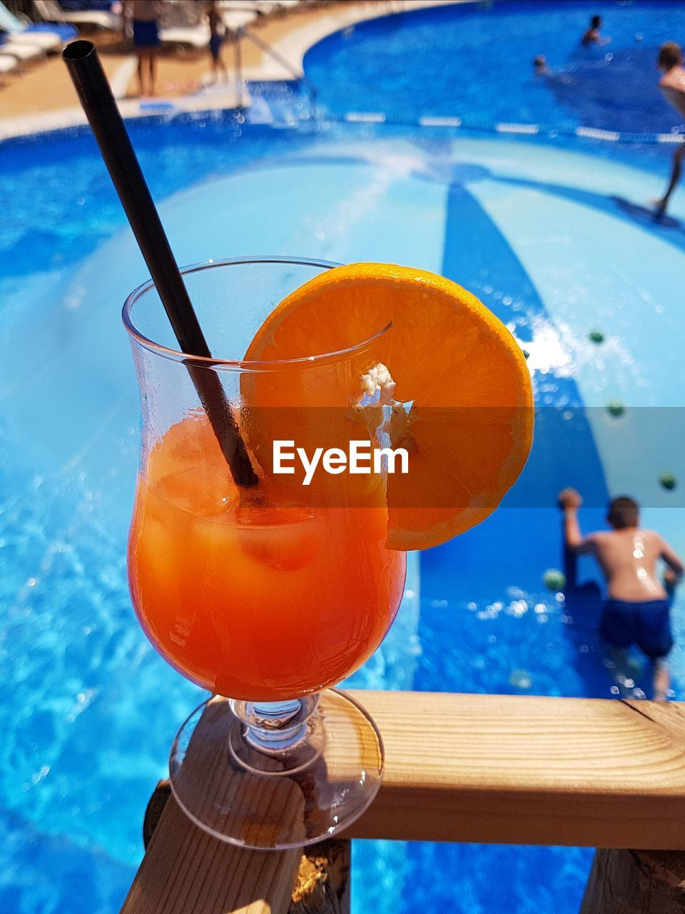 drink, food and drink, glass, refreshment, straw, drinking glass, cocktail, food, drinking straw, alcohol, household equipment, focus on foreground, fruit, healthy eating, freshness, close-up, orange color, table, day, outdoors, swimming pool, orange, tropical drink