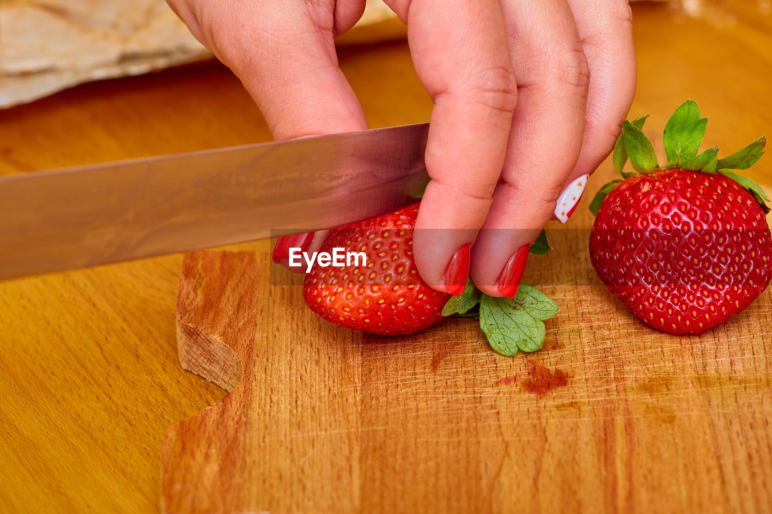 MIDSECTION OF PERSON HOLDING STRAWBERRY ON TABLE