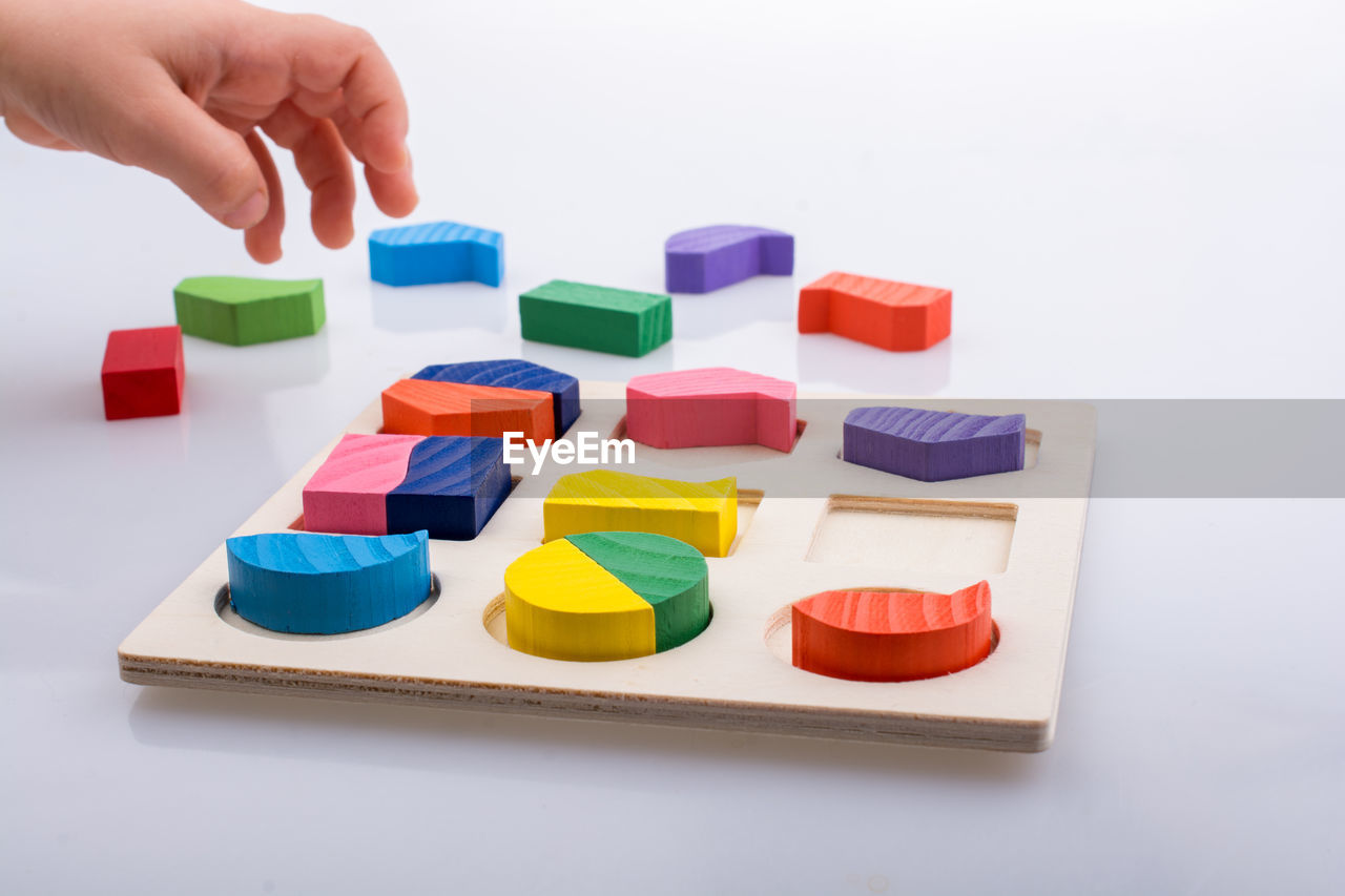 multi colored, human hand, childhood, toy, one person, white background, indoors, hand, human body part, studio shot, toy block, leisure activity, choice, real people, block, variation, large group of objects, arrangement, child, finger
