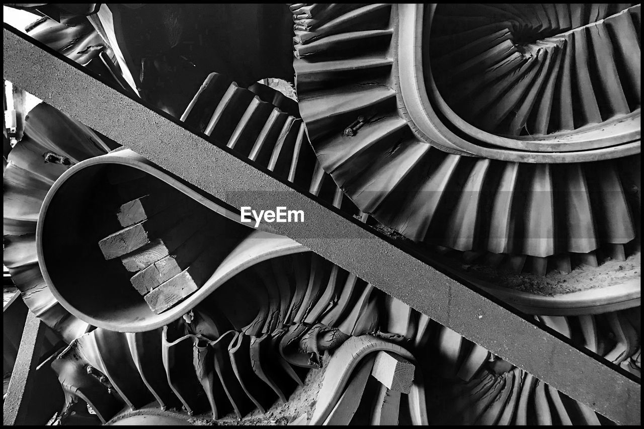 full frame, backgrounds, no people, pattern, metal, large group of objects, indoors, close-up, architecture, high angle view, stack, built structure, still life, technology, machine part, industry, equipment, machinery, staircase, spiral, wheel