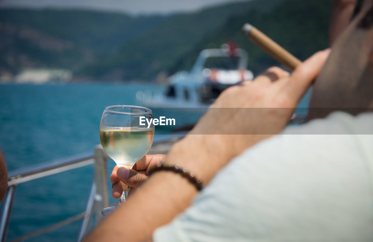 Close-Up Of Hand Holding Wineglass Over River Against Sky