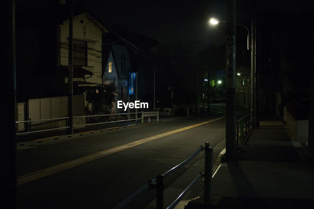 EMPTY ROAD AGAINST ILLUMINATED STREET LIGHTS IN CITY