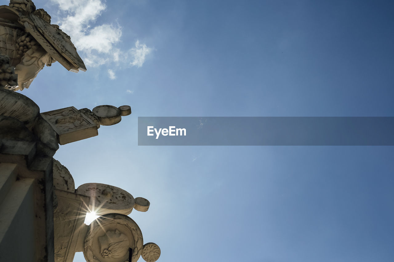 sky, low angle view, cloud - sky, nature, architecture, sculpture, no people, religion, spirituality, day, statue, built structure, belief, representation, human representation, place of worship, blue, art and craft, building exterior, ornate