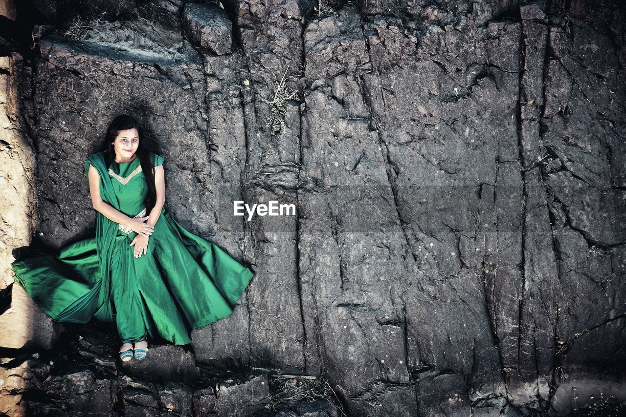 Portrait Of Smiling Woman Wearing Green Dress While Standing On Rock Formation