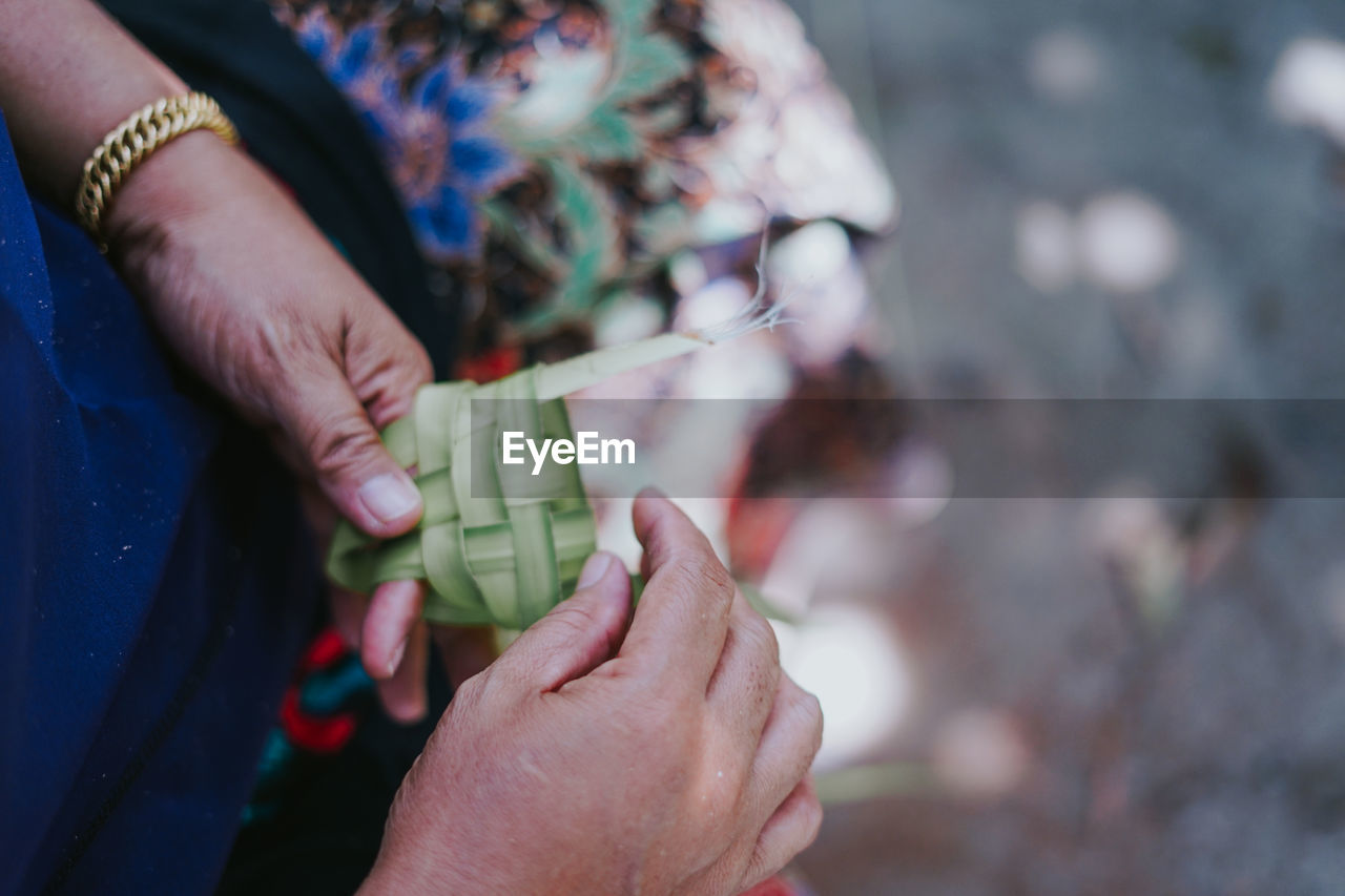 human hand, hand, human body part, real people, holding, focus on foreground, people, women, lifestyles, adult, day, high angle view, body part, close-up, two people, selective focus, leisure activity, outdoors, child, finger, care
