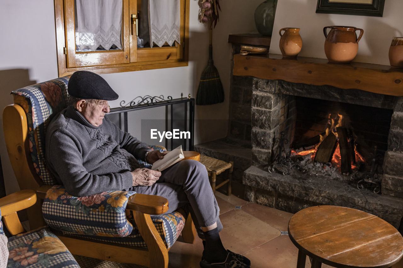 High angle view of man reading book while sitting by fireplace at home