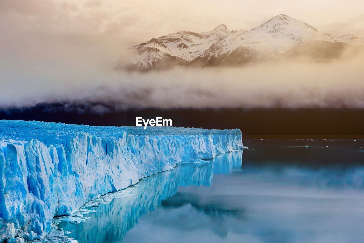 Scenic view of iceberg in water against snowcapped mountains during winter