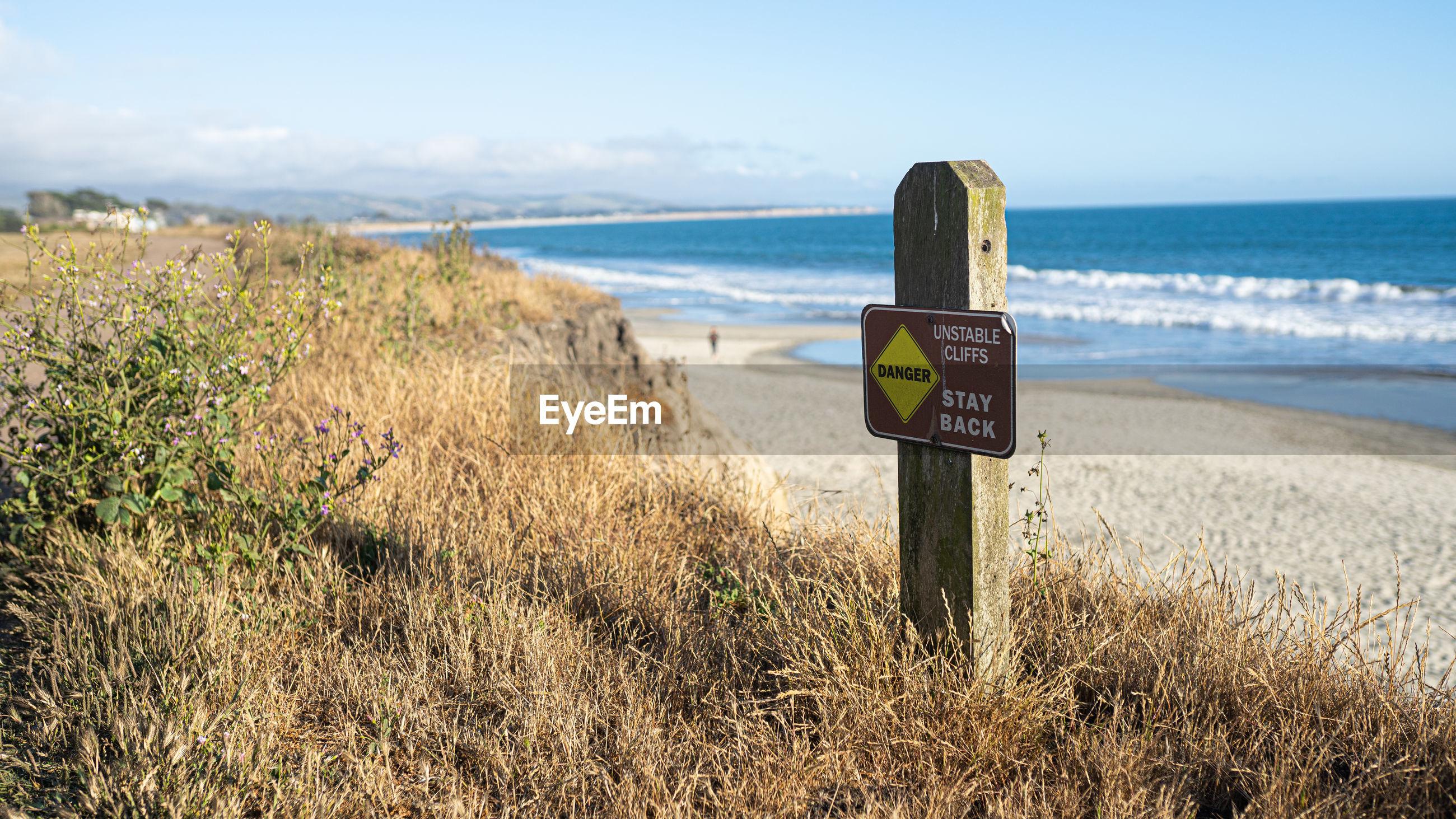 SIGN ON BEACH AGAINST SKY