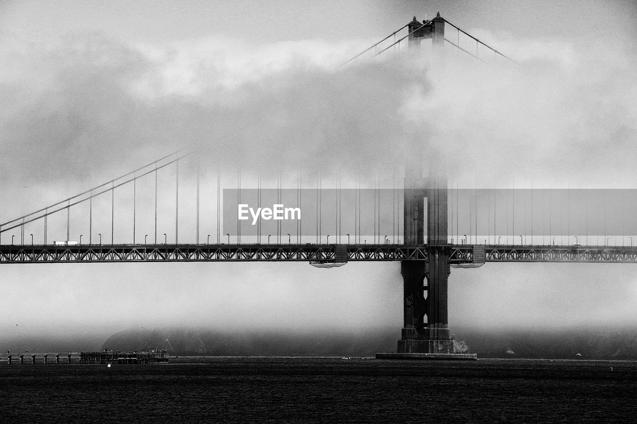 Low angle view of golden gate bridge over river against sky during foggy weather
