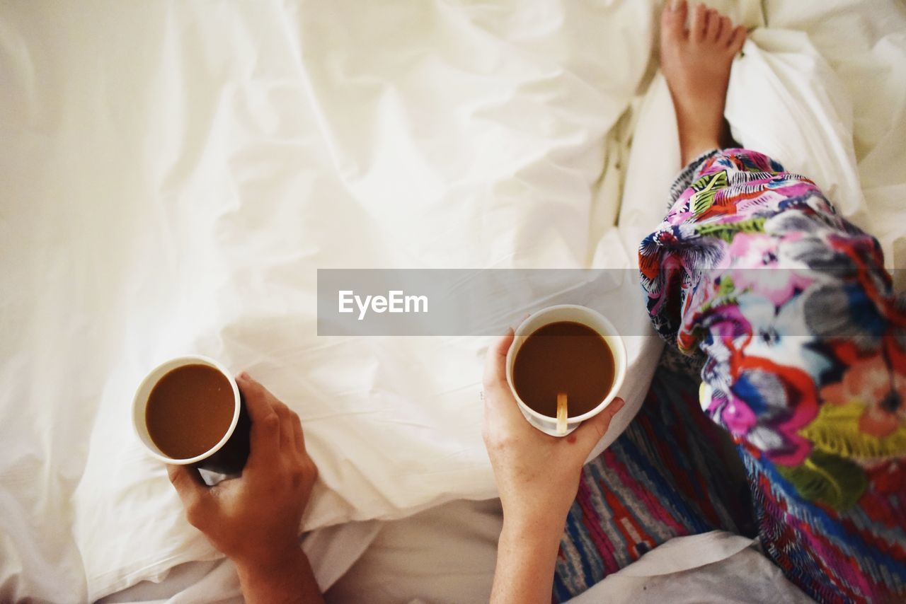 Low section of couple holding coffee cup on bed