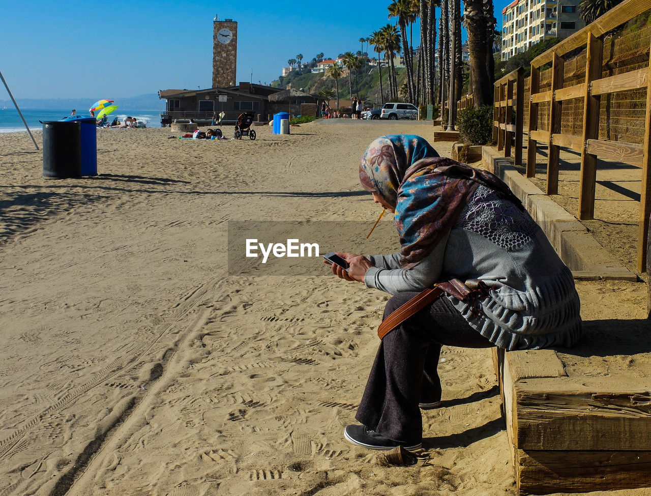Woman Wearing Hijab Using Cell Phone At Beach