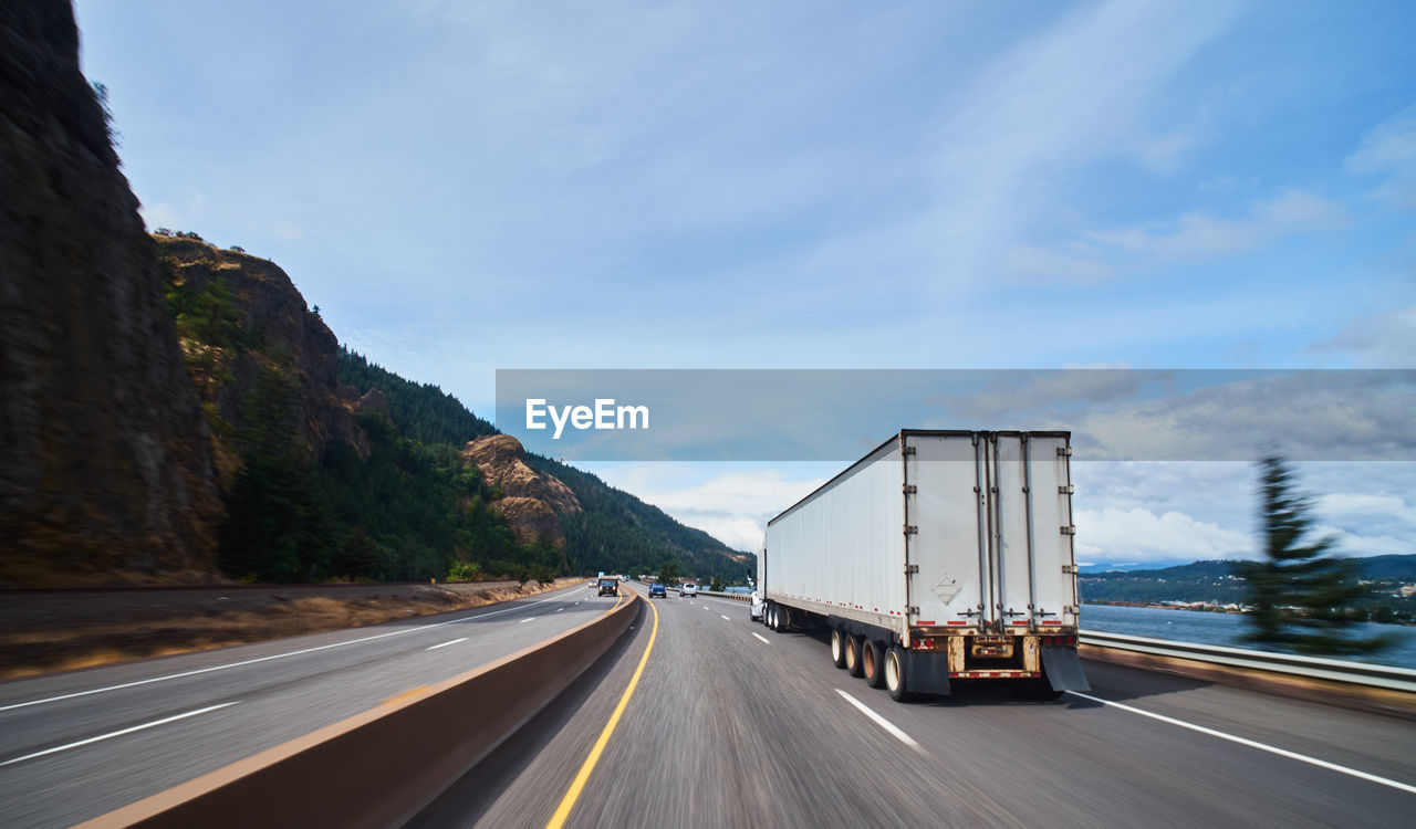 road, transportation, sky, mountain, truck, motion, cloud - sky, the way forward, land vehicle, nature, mode of transportation, direction, semi-truck, highway, on the move, day, symbol, motor vehicle, no people, sign, diminishing perspective, outdoors