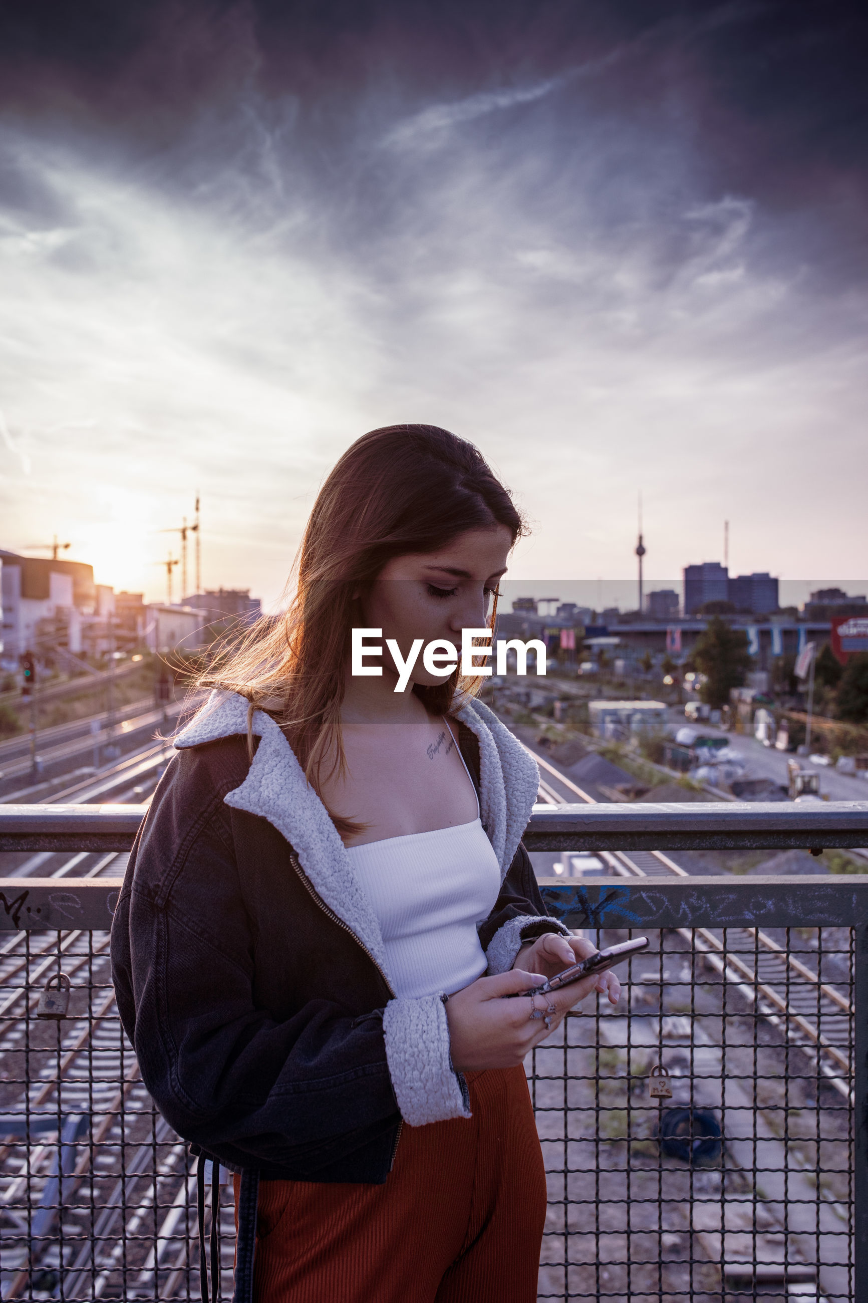 Young woman using phone on bridge against sky