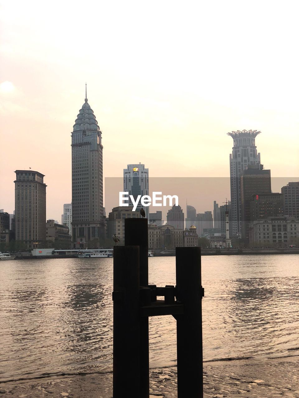 built structure, architecture, building exterior, water, sky, city, building, waterfront, office building exterior, skyscraper, tower, urban skyline, river, tall - high, landscape, travel destinations, nature, sunset, no people, cityscape, outdoors, modern, financial district, spire