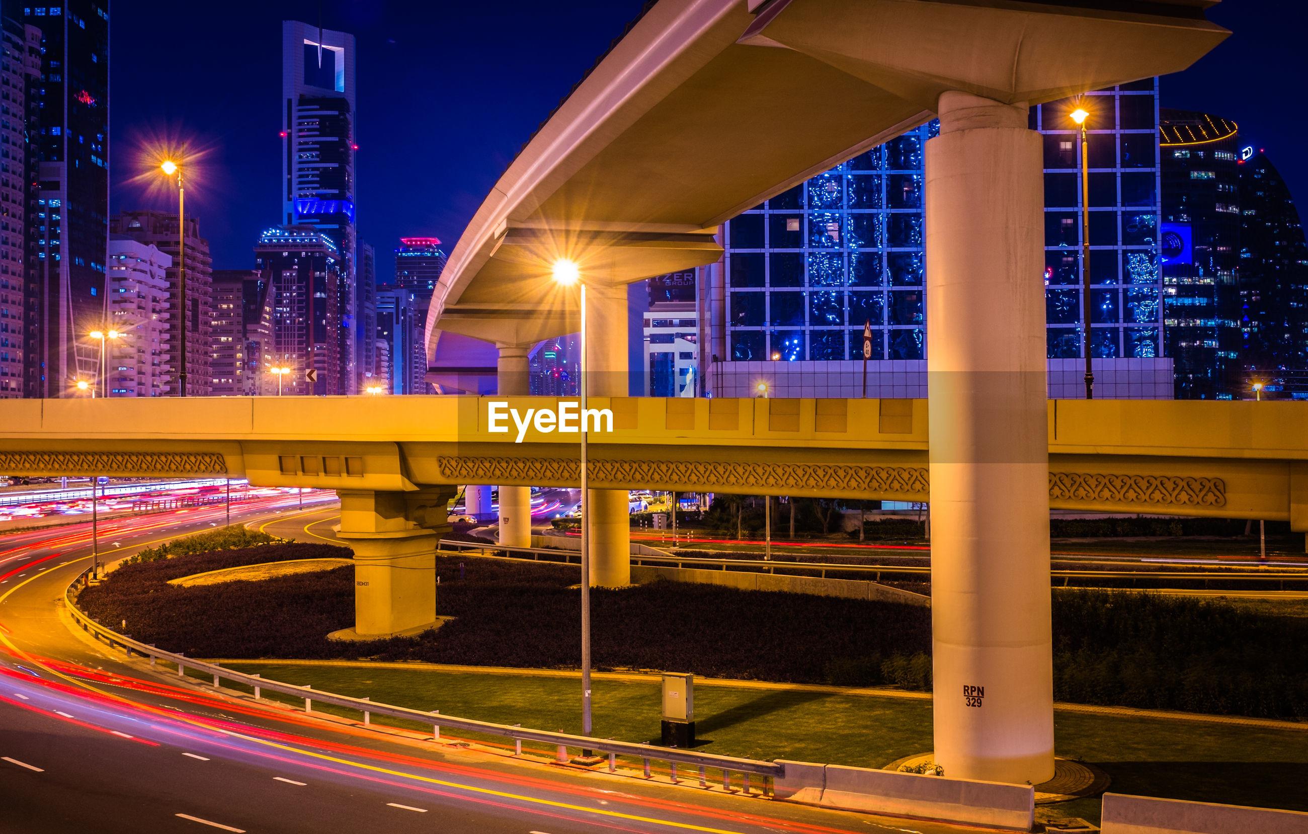 Light trails by illuminated bridge in city at night