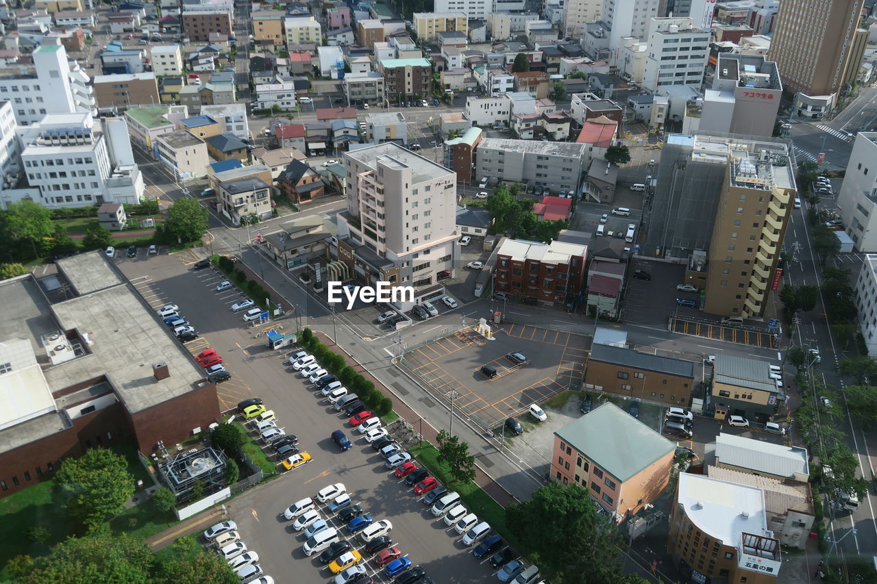 building exterior, city, architecture, built structure, transportation, high angle view, car, street, mode of transportation, motor vehicle, building, road, cityscape, land vehicle, residential district, traffic, day, city life, crowded, outdoors, city street, apartment