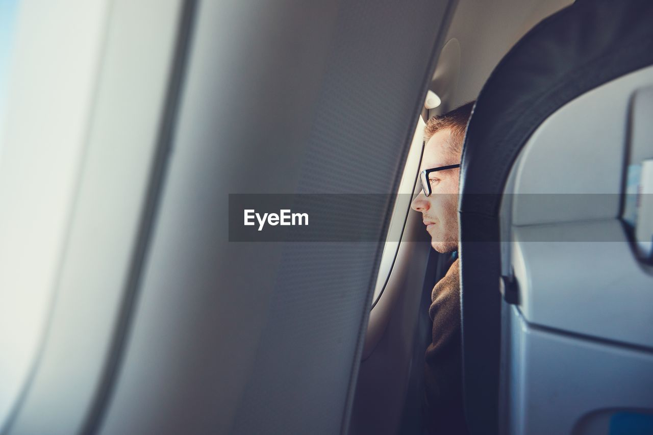Man Looking Through Airplane Window