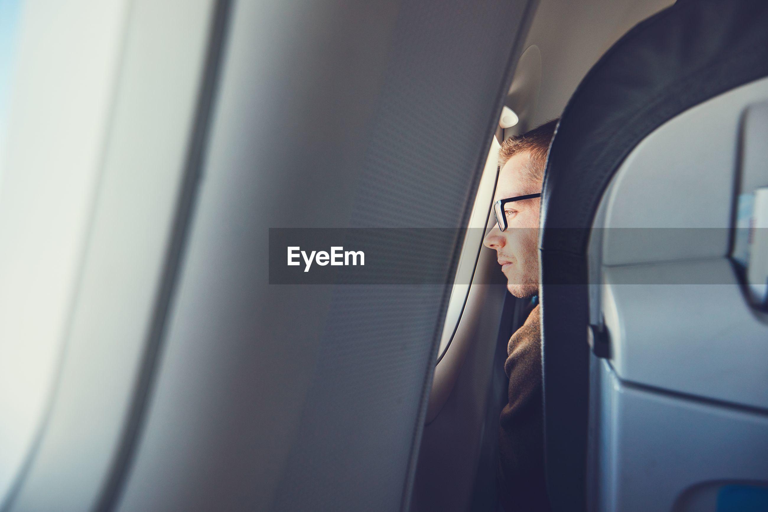 Man looking through airplane window