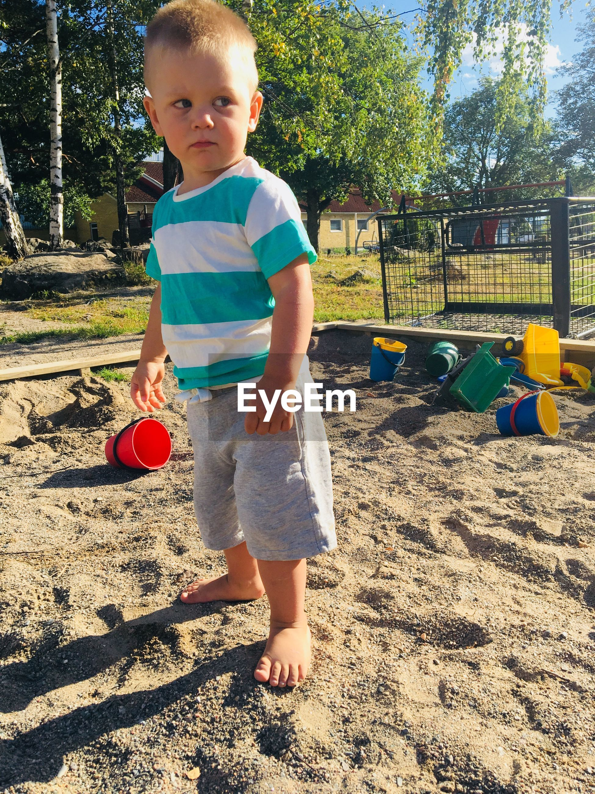 Cute boy standing on sand in playground