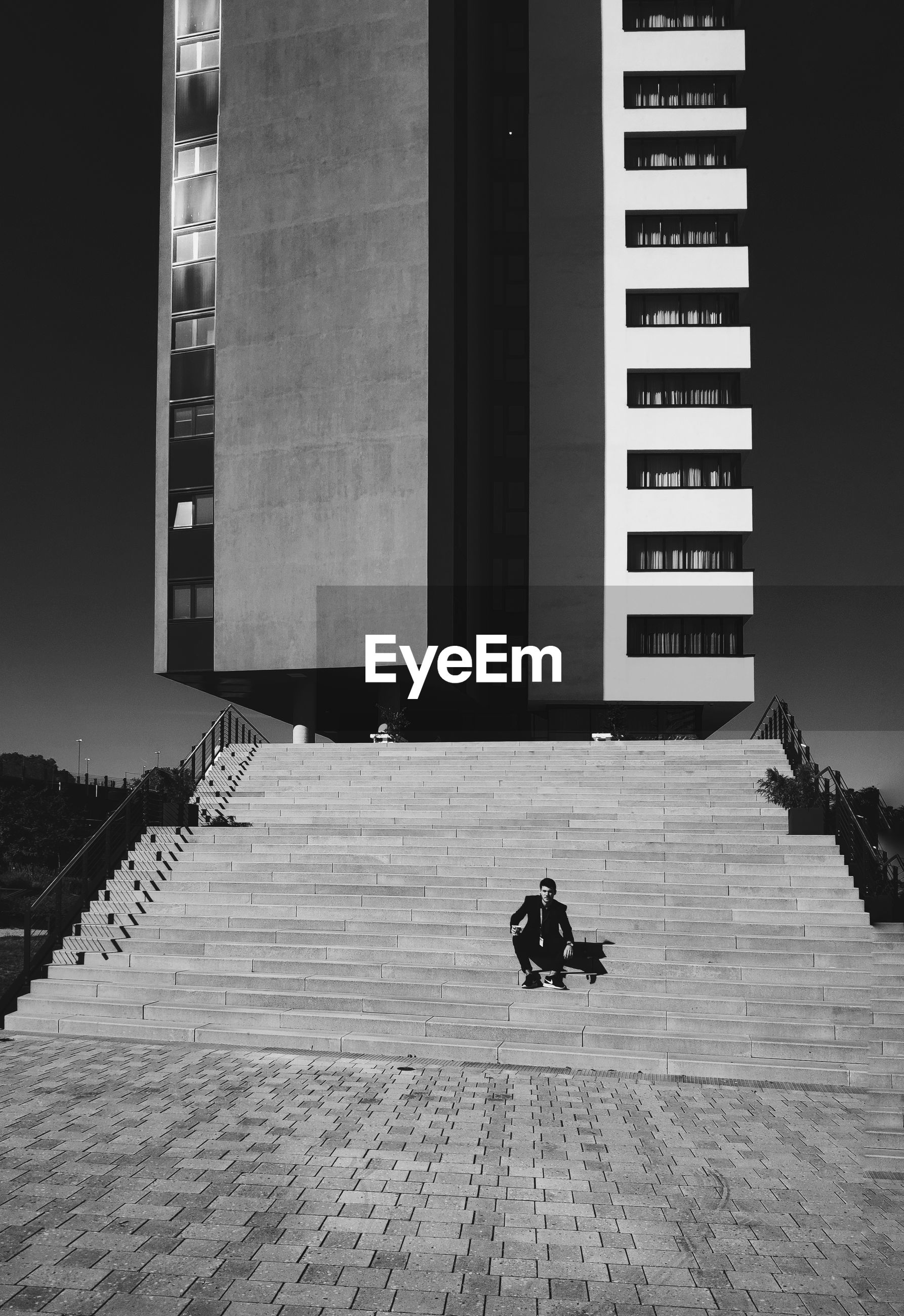 Man sitting on staircase against building