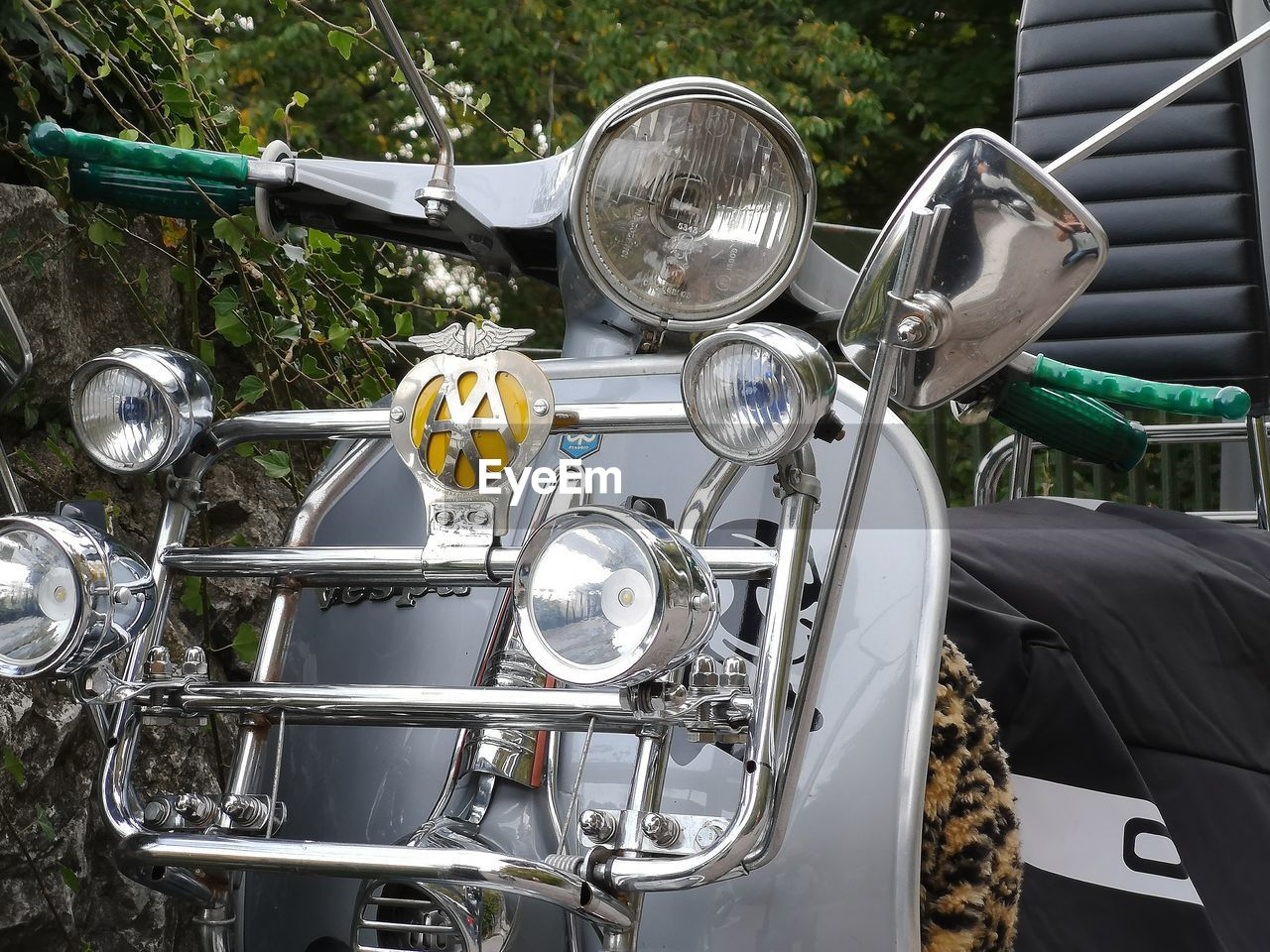 transportation, mode of transportation, land vehicle, headlight, stationary, metal, day, no people, motorcycle, close-up, outdoors, bicycle, retro styled, car, motor vehicle, shiny, focus on foreground, handlebar, parking, chrome, silver colored
