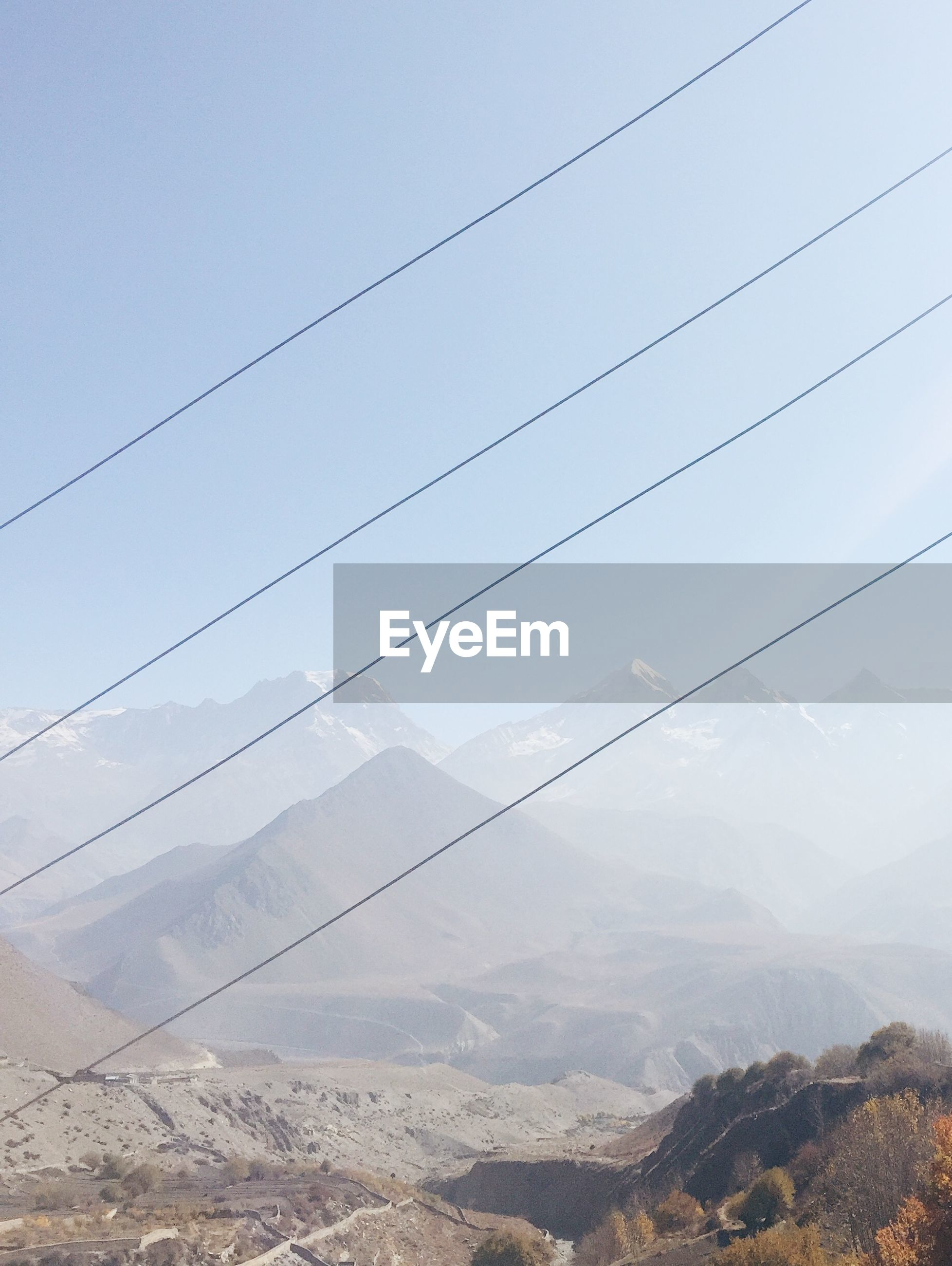 Scenic view of annapurna range against sky seen through cables