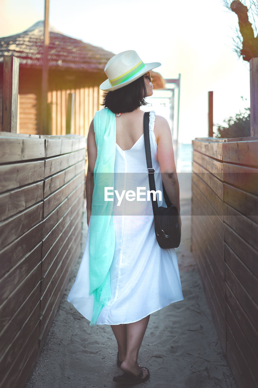 one person, real people, hat, leisure activity, architecture, clothing, lifestyles, built structure, standing, casual clothing, rear view, day, holding, building exterior, technology, fashion, full length, wall - building feature, camera - photographic equipment, outdoors, shorts