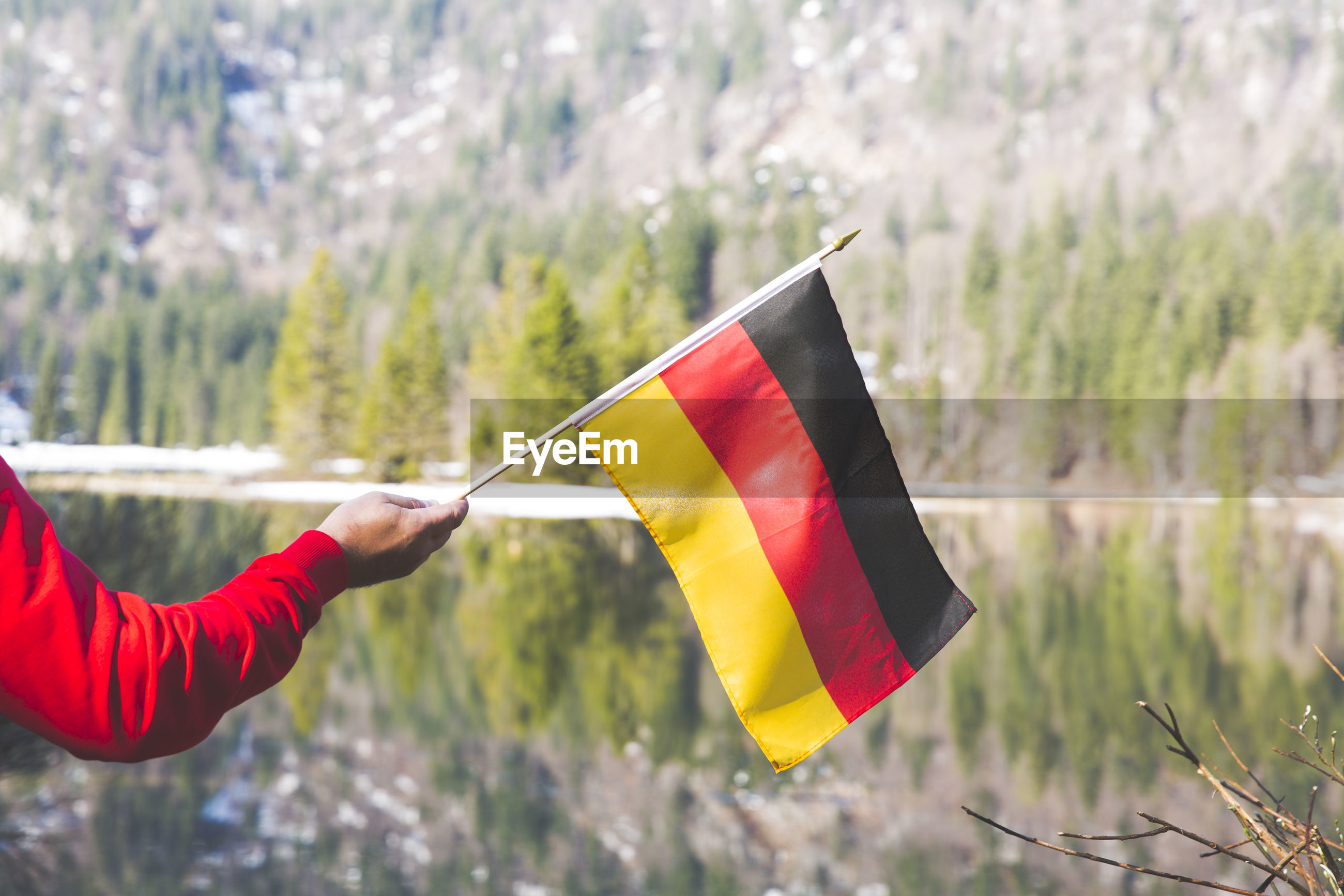 Cropped hand holding german flag at lakeshore