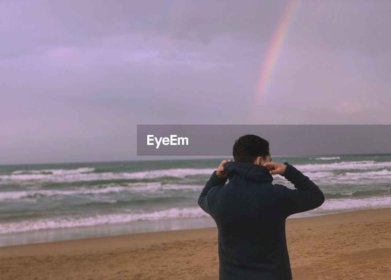 sea, water, sky, horizon, beach, one person, beauty in nature, land, horizon over water, standing, scenics - nature, real people, rainbow, rear view, cloud - sky, lifestyles, leisure activity, nature, outdoors, photographer