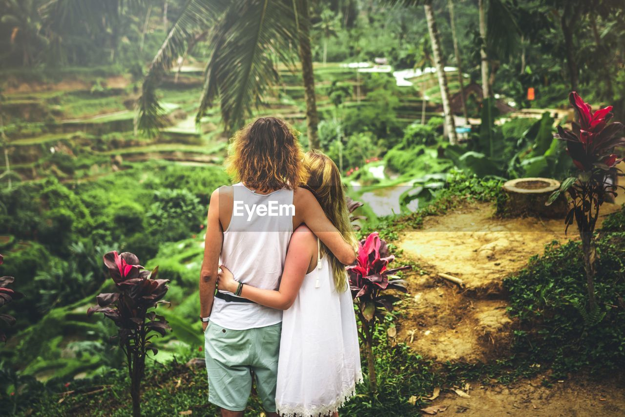 plant, rear view, real people, flower, nature, women, flowering plant, three quarter length, lifestyles, tree, growth, day, leisure activity, beauty in nature, people, casual clothing, adult, outdoors, standing, hairstyle