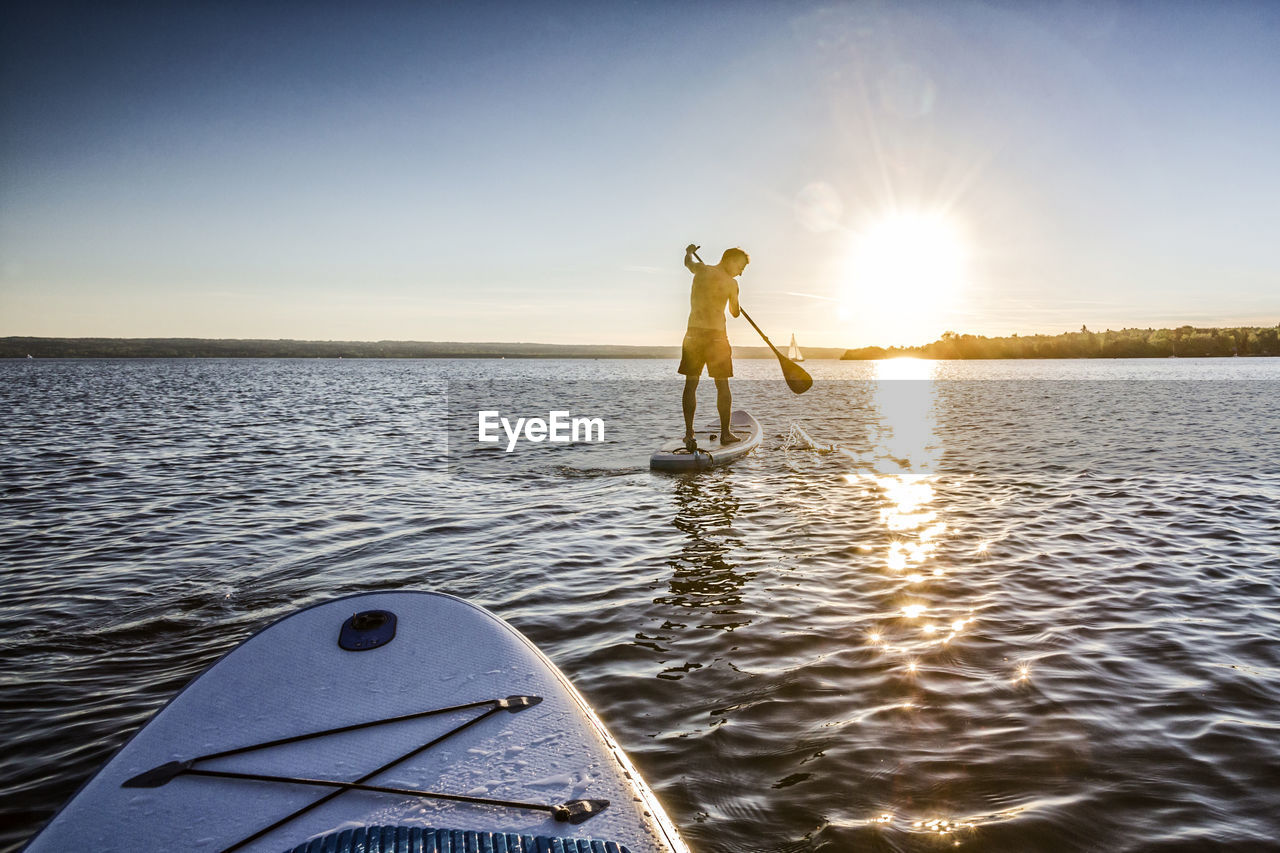 Man Paddleboarding In Sea Against Sky During Sunset