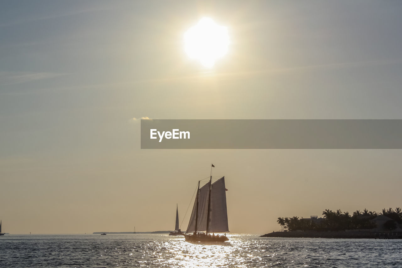 sun, sky, lens flare, sunset, sunlight, sailboat, water, nautical vessel, sea, sailing, beauty in nature, outdoors, no people, nature, tranquility, waterfront, scenics, mast, day