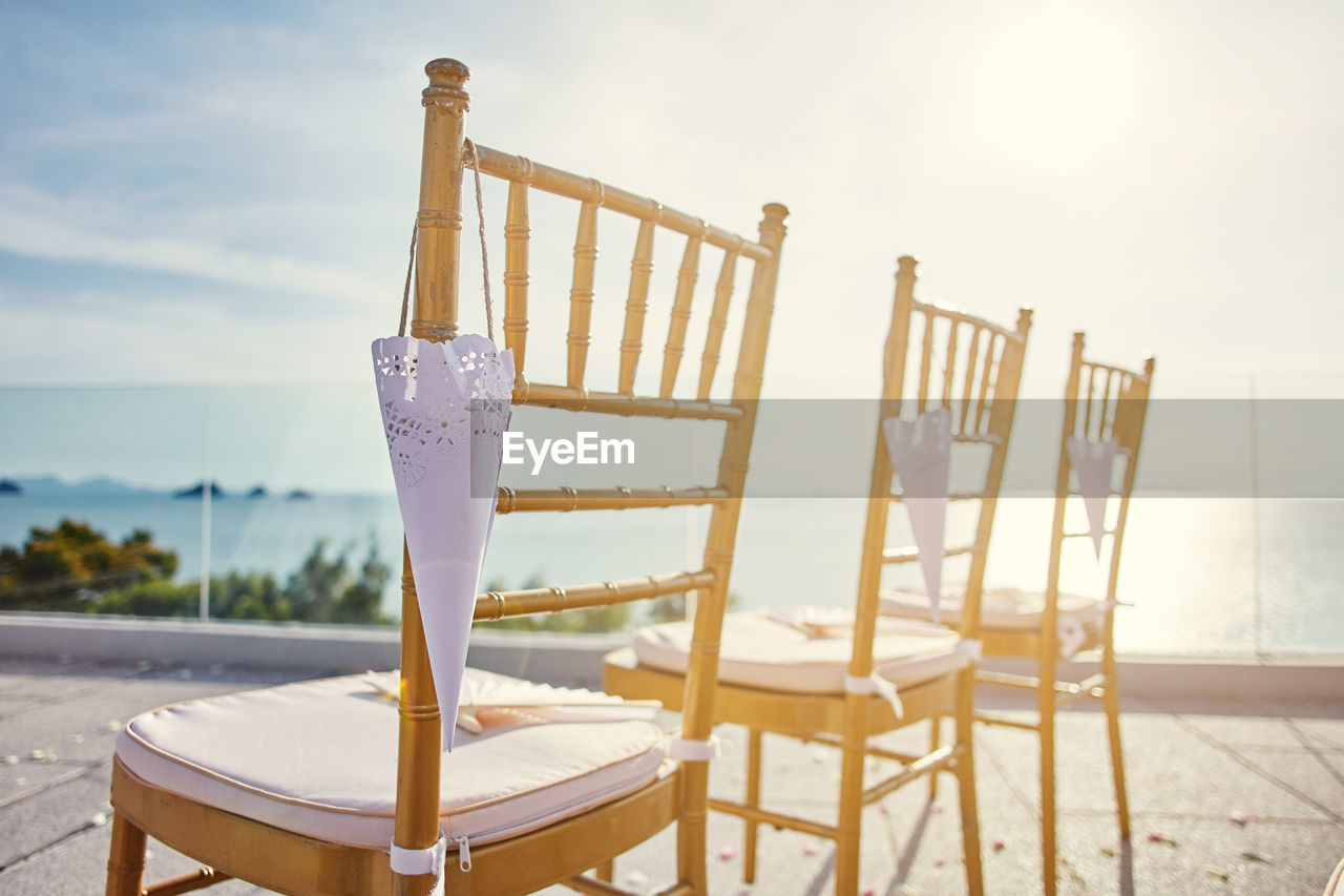 chair, seat, focus on foreground, no people, sky, absence, table, nature, day, sunlight, wood - material, outdoors, close-up, railing, communication, still life, empty, water, beach, barrier