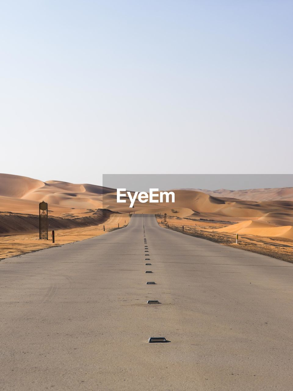 Empty road leading towards sand dunes at desert against clear sky