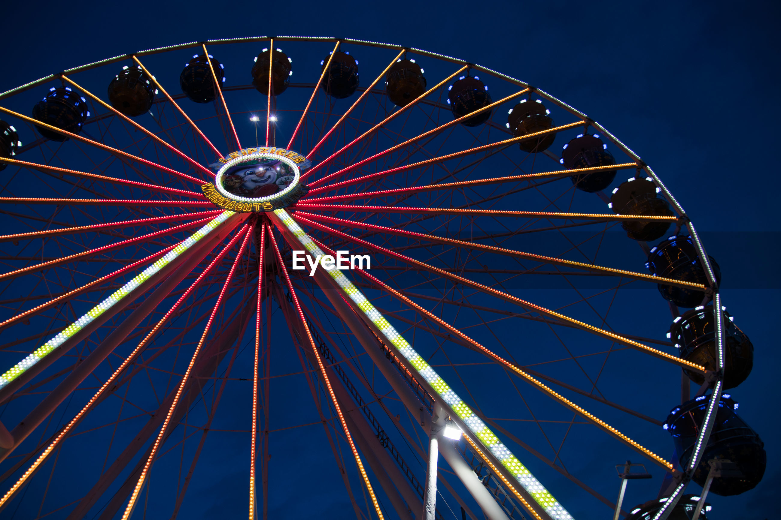 LOW ANGLE VIEW OF ILLUMINATED FERRIS WHEEL AGAINST CLEAR SKY